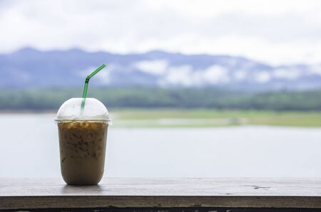 Glass of cold espresso coffee on the table Background blurry views sky water and mountain.