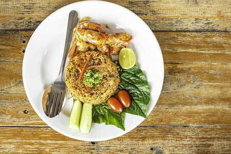 Fried rice with spicy shrimp on wooden table ,  food Thai style.