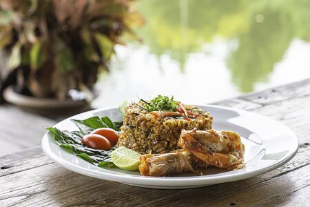 Fried rice with Shrimp on wooden table , spicy food Thai style Background rivers and trees.