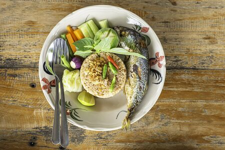 Fried rice with chili spicy with fish and vegetables in white plate on wooden table. Stock Photo