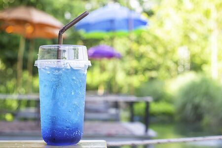 Glass of Italian soda cold on wooden table Background blurry views tree.
