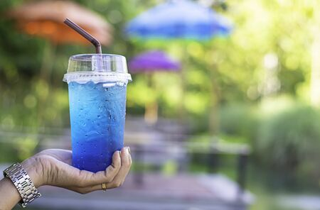 Hand holding a glass of Italian soda cold Background blurry views tree.