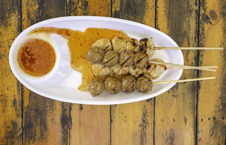 Grilled pork and beef meatballs with seafood sauce on white plastic plate. Stock Photo