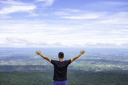 Asian man raise their arms on the point of view of the mountains at Patio stone button in Phu Hin Rong Kla National Park ,Phitsanulok , Thailand. Stock Photo