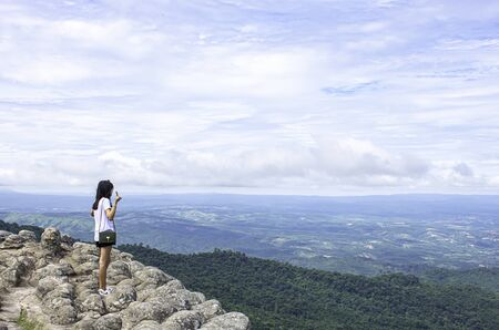Asian woman raise their arms on the point of view of the mountains at Patio stone button in Phu Hin Rong Kla National Park ,Phitsanulok , Thailand. Stock Photo