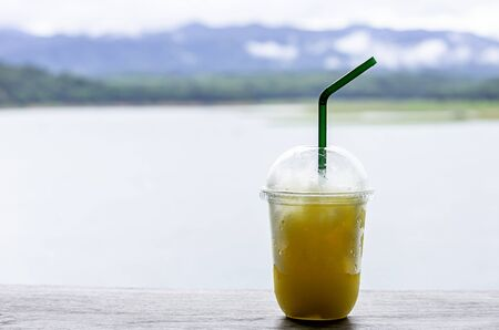 Glass of cold Orange juice smoothie on the table Background blurry views sky water and mountain. Stock Photo