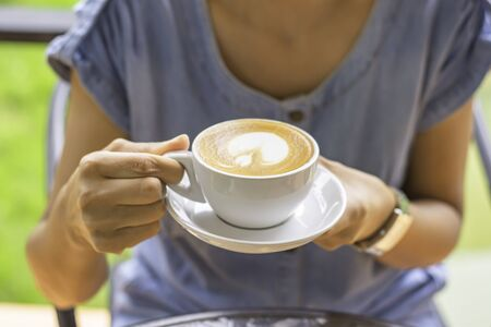 Hands holding white coffee cup with saucer.