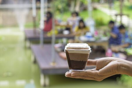 Hand holding cake Background blur people and tree in garden on pond. Stock Photo