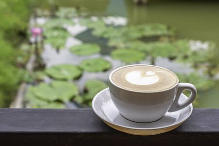Coffee Mugs white plate with The heart shaped makeup on  iron balconies  Background Lotus pond.
