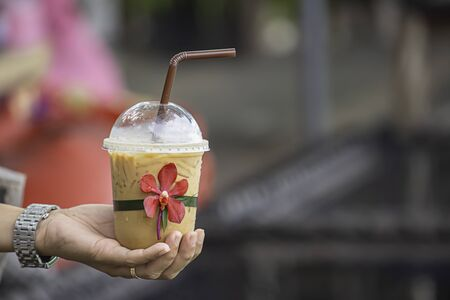 Hand holding a glass of cold espresso coffee with red orchid flower Background blurry views.