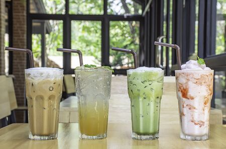 Iced Coffee, Honey Lemon Soda , iced green tea and strawberry smoothie in glass on the wooden table Background glass windows and  tree. Stock Photo