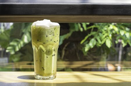 Iced green tea  in glass on the wooden table Background glass windows and  tree.