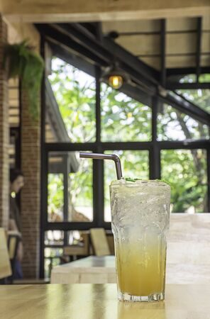 Honey Lemon Soda in glass on the wooden table Background glass windows and  tree.