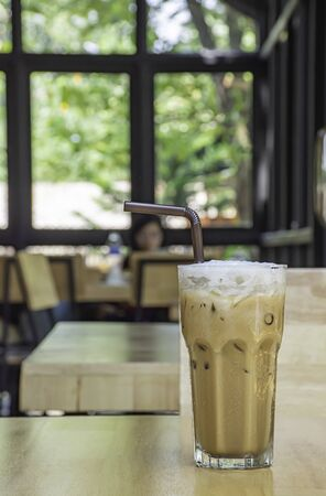 Iced Coffee in glass on the wooden table Background glass windows and  tree.