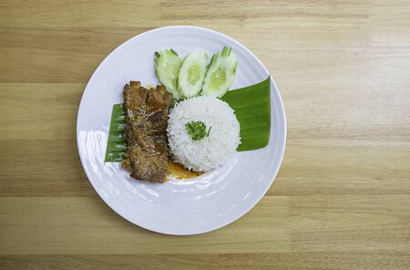 Rice and Pork Ribs On banana leaves With cucumbers on a white plate on wooden  table. Stock Photo