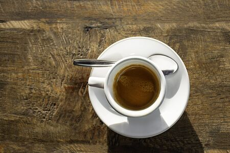 Top view Hot coffee in a white cup with saucer on a wooden table. Stockfoto