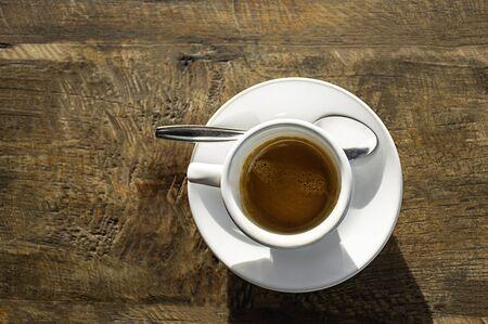 Vista superior Café caliente en una taza blanca con platillo sobre una mesa de madera. Foto de archivo