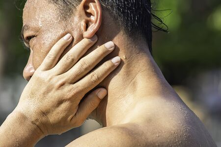 The hand grips the neck that inflammation from a sports injury.