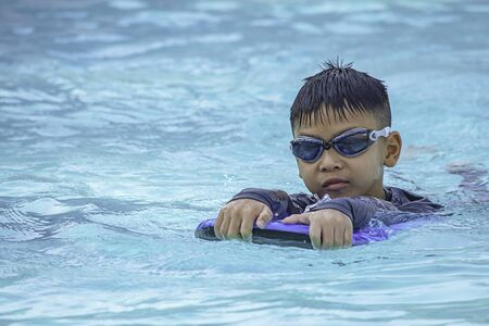 Asian boy learned to swim in the pool.