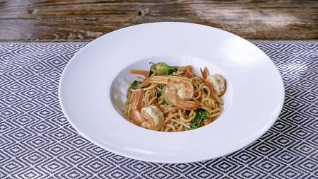The spaghetti spicy shrimp in a white plate on the tablecloth. Banque d'images