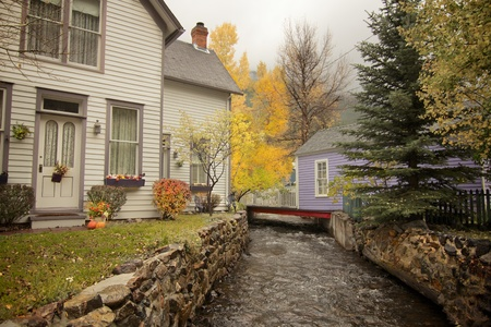 pine trees: Small stream running between homes in mountain town with pine trees Stock Photo
