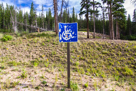handicap sign: Blue Handicap Parking Sign Shot with bullet holes and Battered in mountain woods