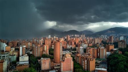 Medellin Colombia Regen storm met wolken naderen stad met gebouwen in schot. Latijns  Zuid-Amerika