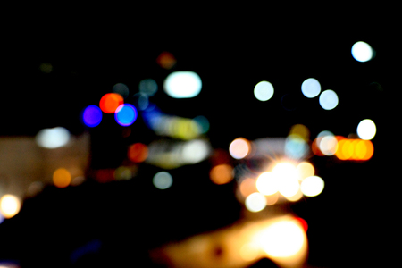 Real Light blur bokeh in dark background from lens out focus. Red blue green yellow light neon at bar.it look like circle light many color blur at night on street in big city in celebration time