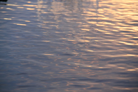fluidity: Water surface at sunset. Glare and reflections of the day.