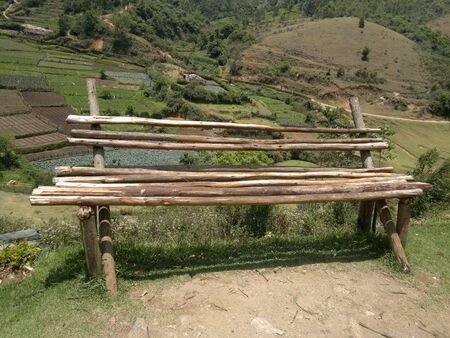 village bench of wooden bars overlooking the agricultural field