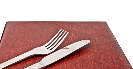 Knife and fork on leather menu cover photo