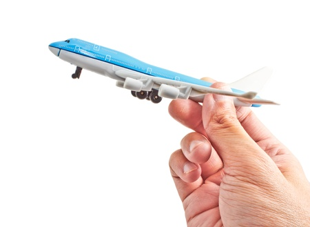miniature people: hand holding a blue commercial model aircraft