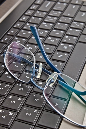 glasses on computer keyboard photo