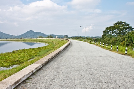 local road beside a dam Stock Photo