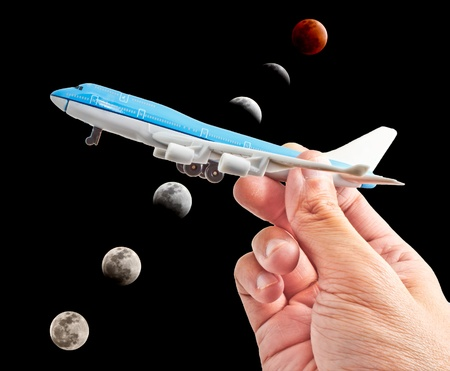 hand holding a model plane with lunar eclipse background photo