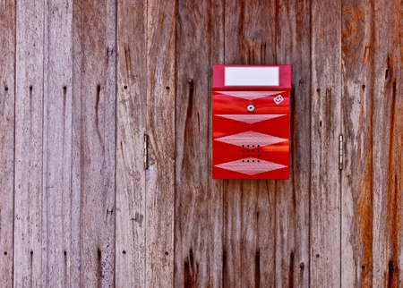 red postbox on a old wooden wall photo