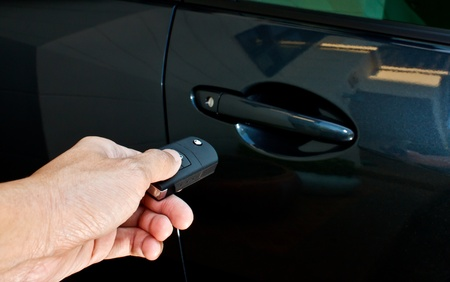 a hand holding a remote control pointing to a car photo