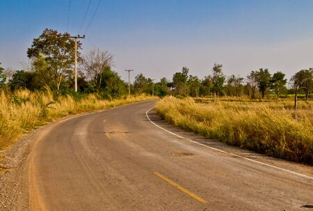 local road to agricultural village in Thailand photo