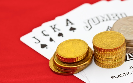 coins and playing cards on red table photo