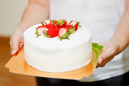 lady holding strawberry cake photo