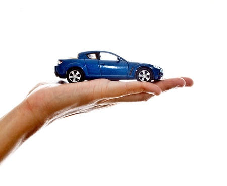 hand holding a blue car model on white background
