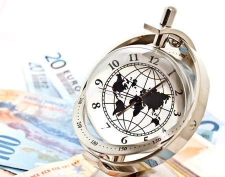 economie: globaal model klok en Euro bankbiljetten op een witte achtergrond