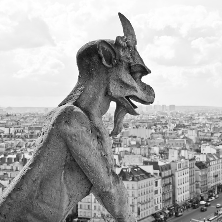 gargoyle: Chimera sculpture and Paris s skyline at the top of Notre Dame Cathedral Stock Photo