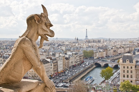 Chimera sculpture and Paris s skyline at the top of Notre Dame Cathedral photo