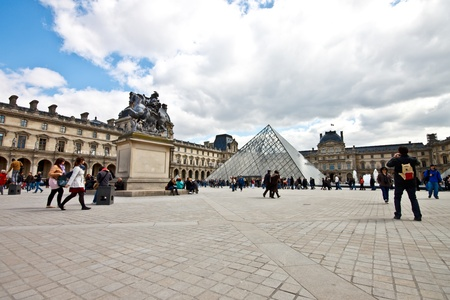 exhibition crowd: Louvre museum with the famous glass pyramid in sunny day