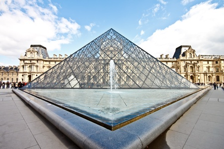 Louvre museum with the famous glass pyramid in sunny day