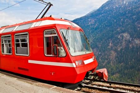 swiss alps: czerwony Szwajcarski pociąg uruchomiony na wzgórzu po stronie kolei
