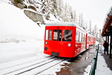Red cog train stop at station during snowing photo