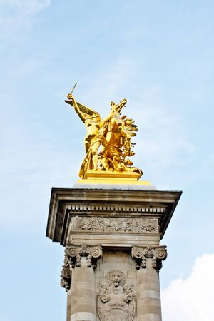 statue at the top of the column at Pont Alexandre III bridge, Paris, France photo