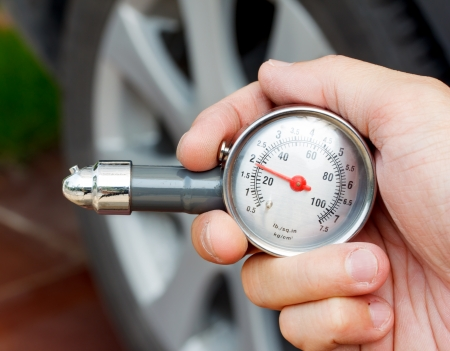 hand holding a tyre pressure gauge photo